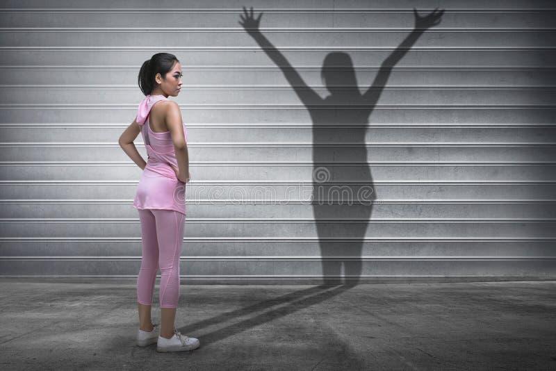 Νέα ασιατική γυναίκα ικανότητας με μια σκιά του πνεύματος στοκ εικόνα