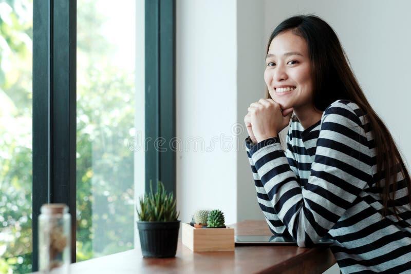 Νέα ασιατική γυναίκα με την ψηφιακή συνεδρίαση ταμπλετών στο υπόβαθρο καφέδων, τους ανθρώπους και τον τρόπο ζωής τεχνολογίας στοκ εικόνες