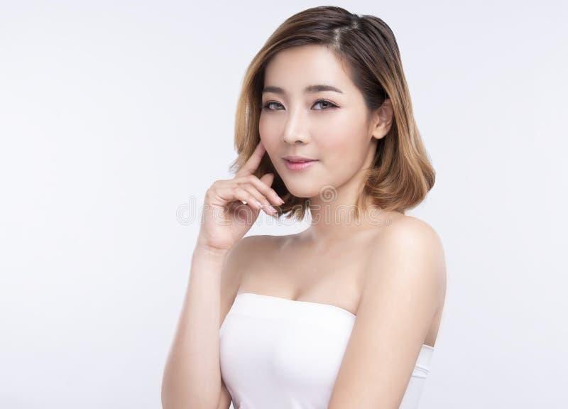 Νέα ασιατική γυναίκα ομορφιάς με το τέλειο του προσώπου δέρμα Χειρονομίες για τη διαφήμιση treatment spa και cosmetology στοκ εικόνα
