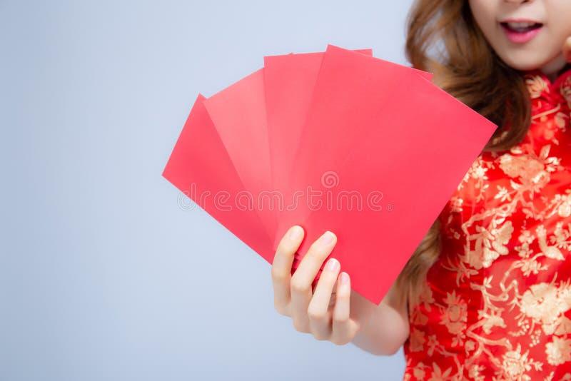 Νέα ασιατική γυναίκα πορτρέτου κινηματογραφήσεων σε πρώτο πλάνο η όμορφη cheongsam ντύνει τον κόκκινο φάκελο εκμετάλλευσης χαμόγε στοκ φωτογραφίες με δικαίωμα ελεύθερης χρήσης
