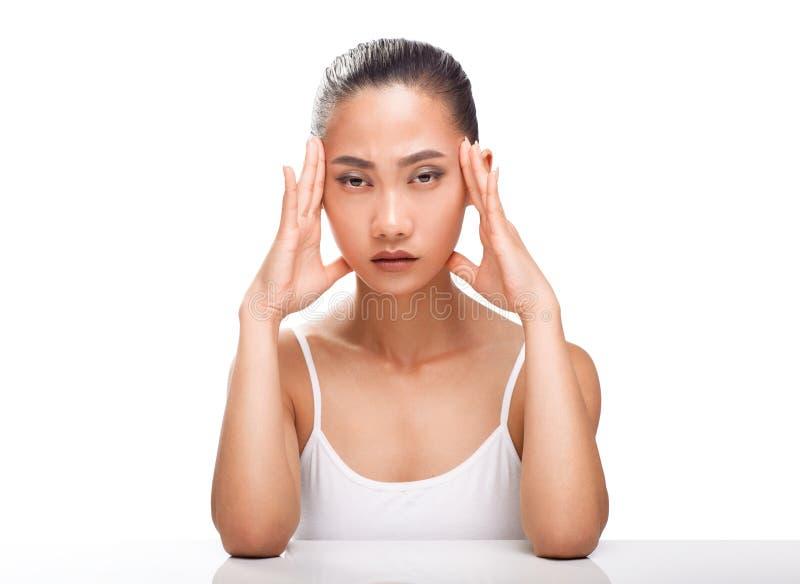 Νέα ασιατική γυναίκα που έχει τον πονοκέφαλο απομονωμένο στο άσπρο υπόβαθρο στοκ φωτογραφία με δικαίωμα ελεύθερης χρήσης