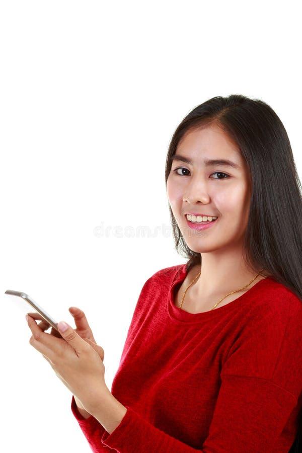 Νέα ασιατική γυναίκα που κρατά το κινητό τηλέφωνο και που παίρνει τη σημείωση με το χαμόγελο στη κάμερα στοκ φωτογραφία με δικαίωμα ελεύθερης χρήσης