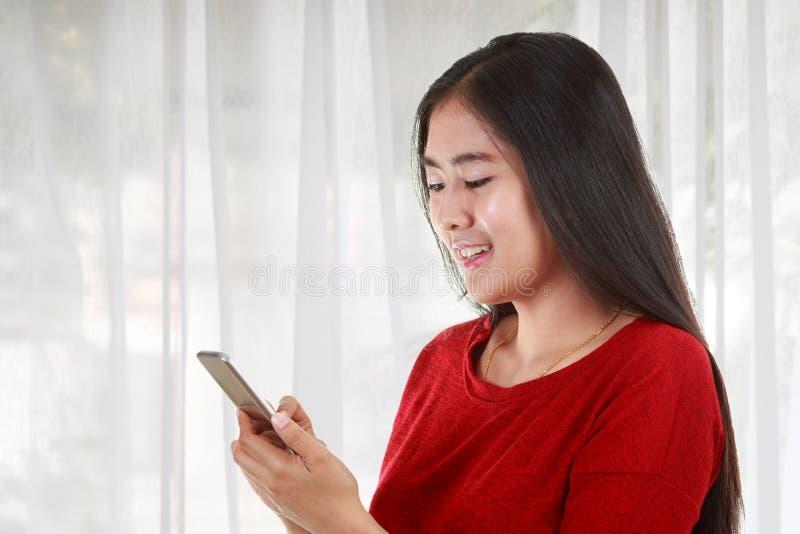 Νέα ασιατική γυναίκα που κρατά το κινητό τηλέφωνο και που παίρνει τη σημείωση στοκ φωτογραφία με δικαίωμα ελεύθερης χρήσης