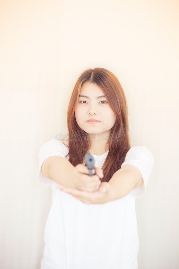 Νέα ασιατική γυναίκα που κρατά το πυροβόλο όπλο στοκ φωτογραφία με δικαίωμα ελεύθερης χρήσης