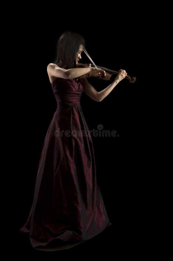 Νέα ασιατική γυναίκα που παίζει το βιολί στο Μαύρο στοκ φωτογραφίες με δικαίωμα ελεύθερης χρήσης