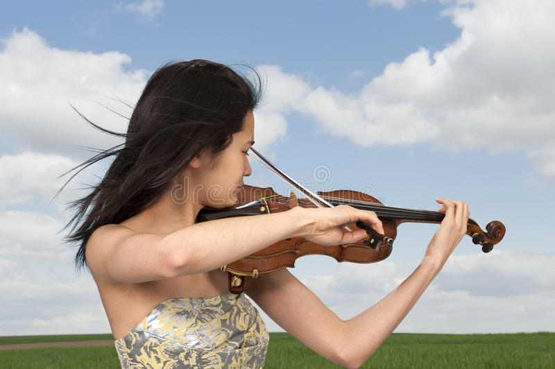 Νέα ασιατική γυναίκα που παίζει το βιολί υπαίθρια στοκ φωτογραφίες με δικαίωμα ελεύθερης χρήσης