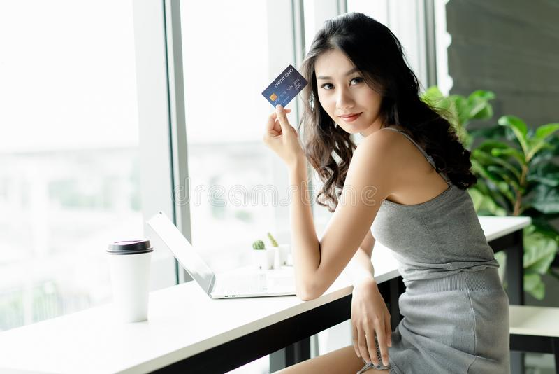 Νέα ασιατική γυναίκα που παρουσιάζει πιστωτική κάρτα στη κάμερα απασχομένος στα WI στοκ εικόνες