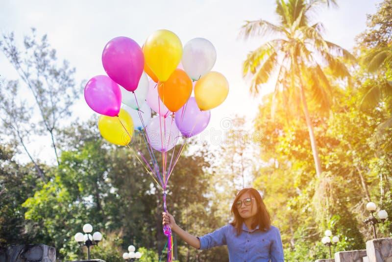Νέα ασιατική γυναίκα που τρέχει και που πηδά στο πράσινο λιβάδι με τα χρωματισμένα μπαλόνια στοκ εικόνες