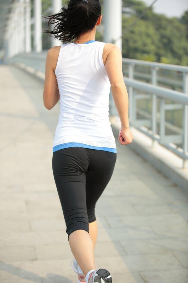 Νέα ασιατική γυναίκα που τρέχει στη σύγχρονη γέφυρα για πεζούς πόλεων στοκ εικόνες με δικαίωμα ελεύθερης χρήσης