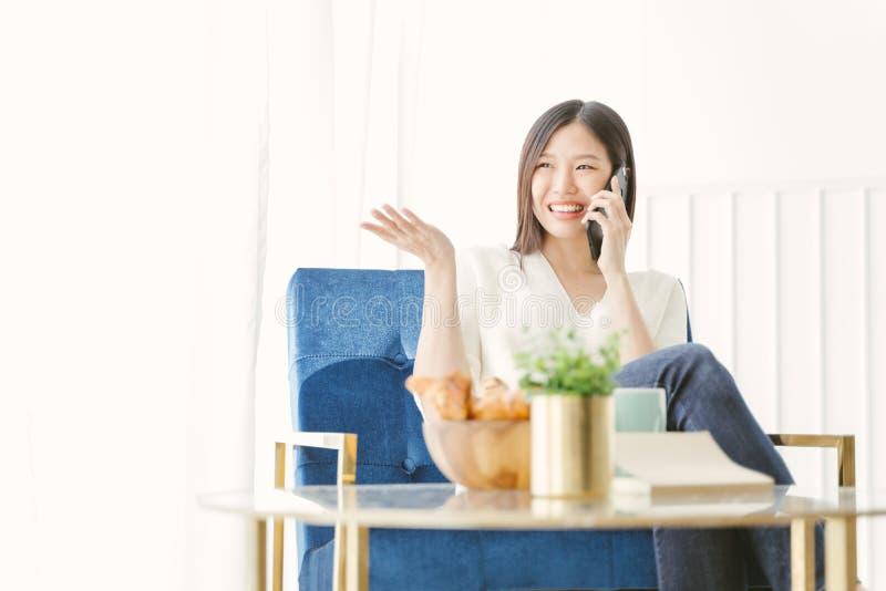 Νέα ασιατική γυναίκα που χρησιμοποιεί την τηλεφωνική ομιλία ευτυχή και το χαμόγελο στοκ φωτογραφία
