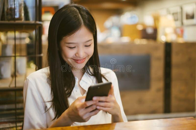 Νέα ασιατική γυναίκα που χρησιμοποιεί το τηλέφωνο σε μια καφετερία ευτυχή και το χαμόγελο στοκ φωτογραφίες με δικαίωμα ελεύθερης χρήσης