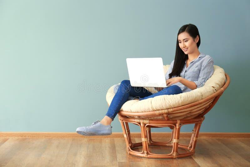 Νέα ασιατική γυναίκα που χρησιμοποιεί το lap-top στην καρέκλα σαλονιών στοκ φωτογραφία