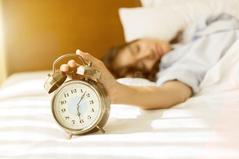 Νέα ασιατική γυναίκα στο κρεβάτι που προσπαθεί ξυπνήστε με το ξυπνητήρι στοκ φωτογραφίες με δικαίωμα ελεύθερης χρήσης