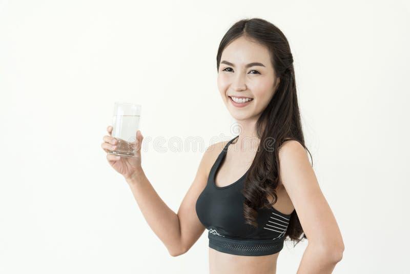 Νέα ασιατική γυναίκα στο μαύρο sportswear ποτήρι κατανάλωσης του νερού επάνω στοκ εικόνα