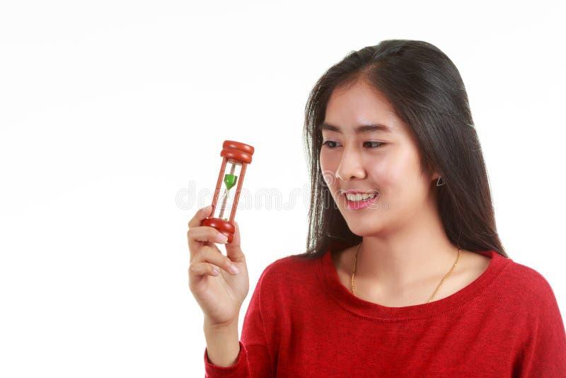 Νέα ασιατική εκμετάλλευση γυναικών και εξέταση την κλεψύδρα με το χαμόγελο στο άσπρο υπόβαθρο στοκ φωτογραφίες