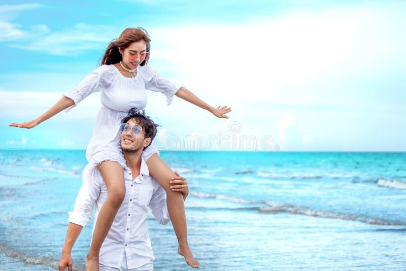 Νέα ασιατική εν πλω παραλία ερωτευμένου μήνα του μέλιτος ζευγών στο μπλε ουρανό νεόνυμφος που δίνει piggyback το γύρο στη νύφη ευ στοκ εικόνες