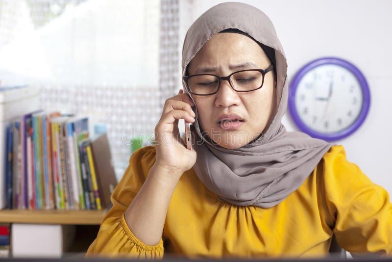 Νέα ασιατική επιχειρηματίας λυπημένη από το τηλεφώνημα στοκ εικόνα