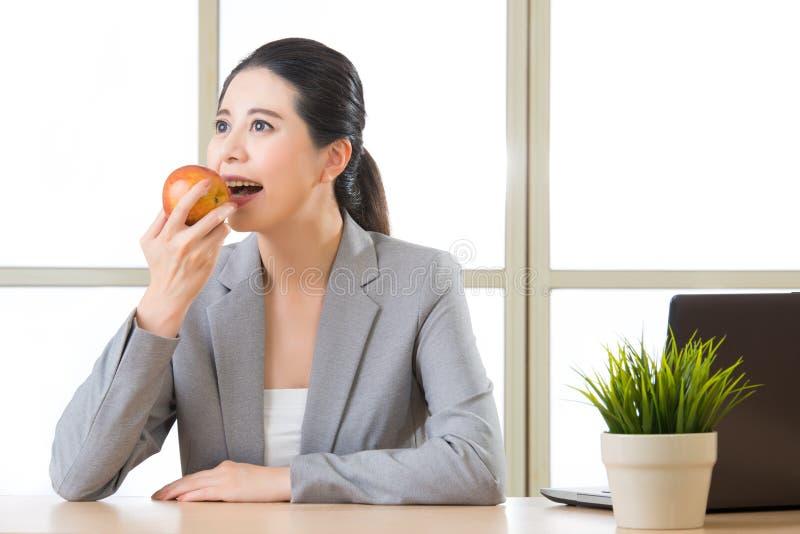 Νέα ασιατική επιχειρηματίας που τρώει το υγιές πρόχειρο φαγητό, μήλο στοκ εικόνες