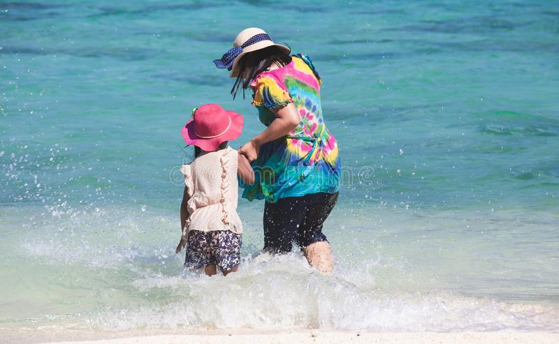 Νέα ασιατική μητέρα και χαριτωμένο νερό παιχνιδιού κορών μαζί στην όμορφη θάλασσα στις θερινές διακοπές στοκ εικόνες