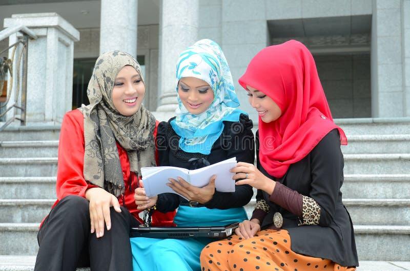 Νέα ασιατική μουσουλμανική γυναίκα στην επικεφαλής μελέτη μαντίλι από κοινού στοκ εικόνες