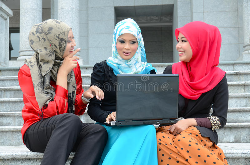 Νέα ασιατική μουσουλμανική γυναίκα στο επικεφαλής μαντίλι με το lap-top στοκ εικόνα
