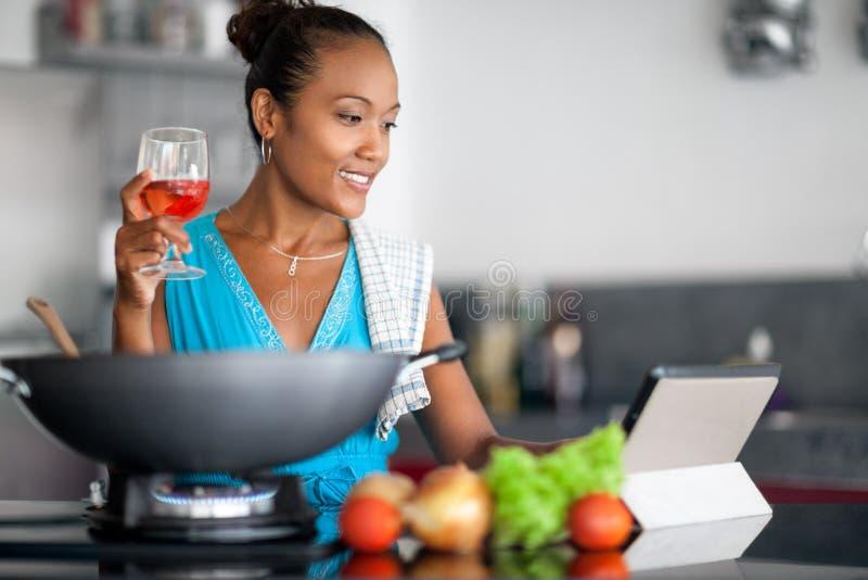 Νέα ασιατική νοικοκυρά που προετοιμάζει τα τρόφιμα και που εξετάζει την ταμπλέτα στοκ φωτογραφία