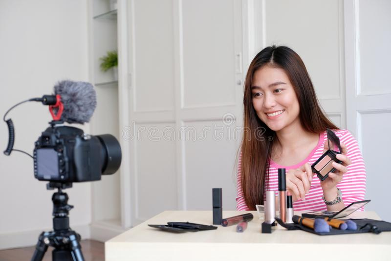 Νέα ασιατική ομορφιά γυναικών blogger που επιδεικνύει πώς να αποτελέσει το τηλεοπτικό TU στοκ εικόνα
