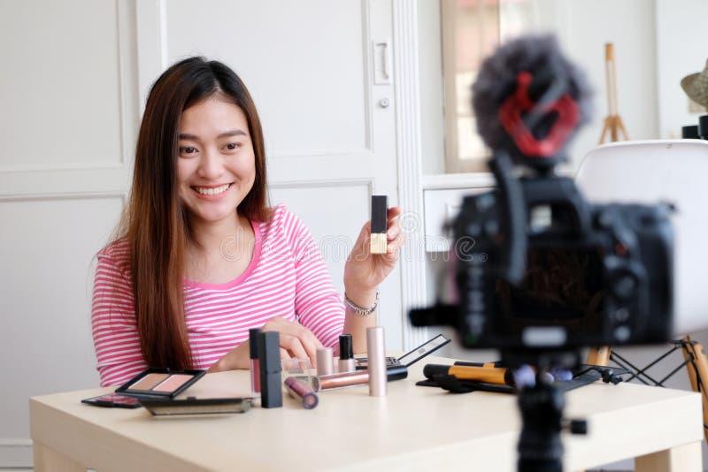 Νέα ασιατική ομορφιά γυναικών blogger που επιδεικνύει πώς να αποτελέσει το τηλεοπτικό TU στοκ φωτογραφίες