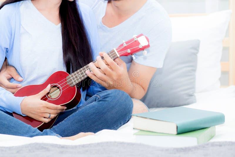 Νέα ασιατική παίζοντας ukulele χαλάρωση ζευγών με την ευτυχία και χαρούμενος στην κρεβατοκάμαρα στοκ φωτογραφίες