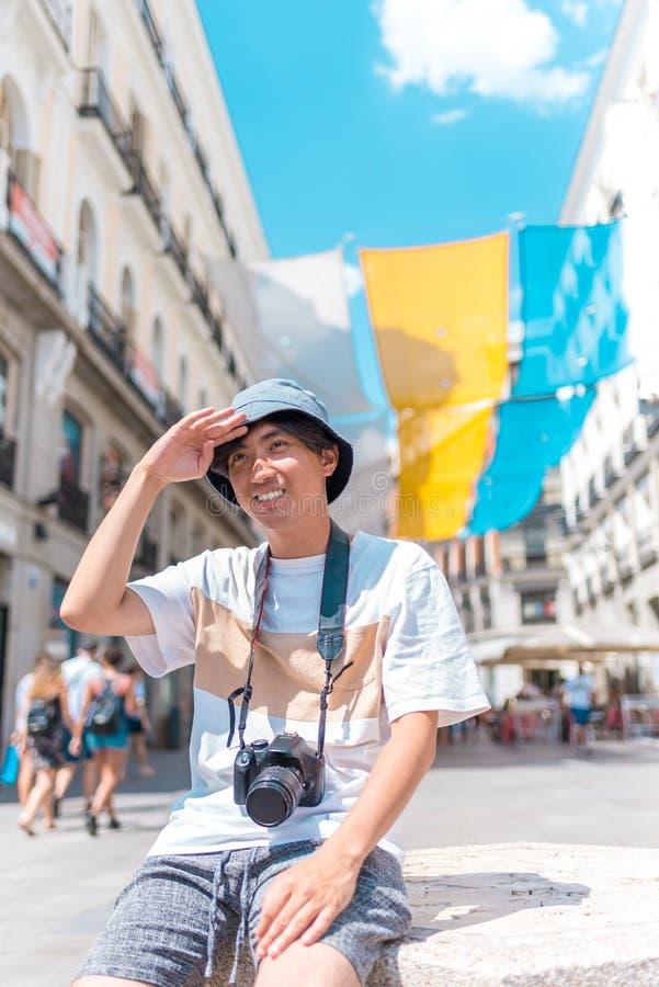 Νέα ασιατική συνεδρίαση ατόμων τουριστών υπαίθρια με μια κάμερα στοκ εικόνα με δικαίωμα ελεύθερης χρήσης