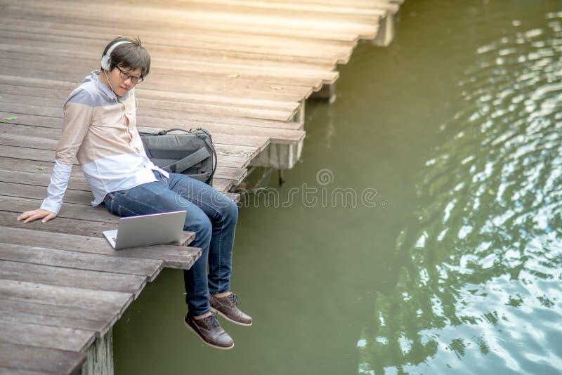 Νέα ασιατική συνεδρίαση ατόμων στη γέφυρα που ακούει τη μουσική στοκ φωτογραφία με δικαίωμα ελεύθερης χρήσης
