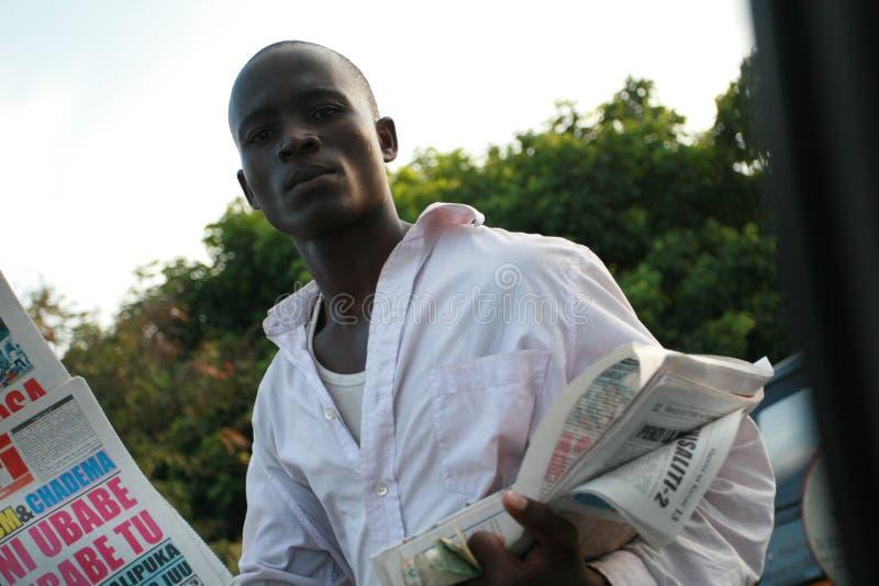Νέα αφρικανικά άτομα, εφημερίδες προσφορών στους οδηγούς στην κυκλοφοριακή συμφόρηση στοκ εικόνες