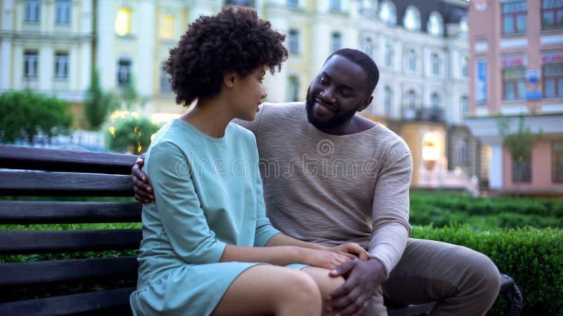 Νέα αφρικανική αγκαλιά ζευγών στον πάγκο στο ηλιοβασίλεμα, ημερομηνία στο πάρκο πόλεων, στενότητα στοκ εικόνες με δικαίωμα ελεύθερης χρήσης
