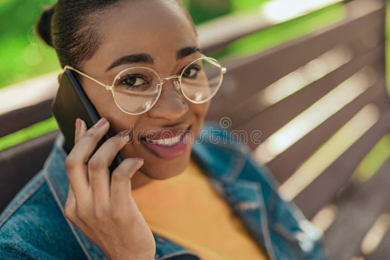 Νέα Αφροαμερικανίδα γυναίκα μιλάει στο σύγχρονο smartphone στοκ φωτογραφίες
