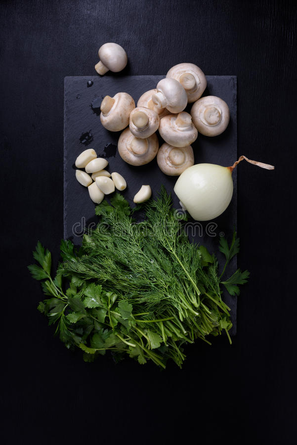 Νέα λαχανικά άνοιξη στον πίνακα πλακών, μαύρο υπόβαθρο Champignons, σκόρδο, άνηθος Επίπεδος βάλτε στοκ εικόνες