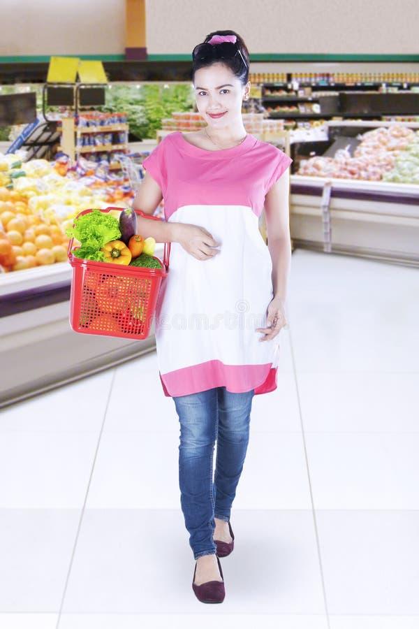 Νέα λαχανικά αγορών γυναικών στο παντοπωλείο στοκ φωτογραφία