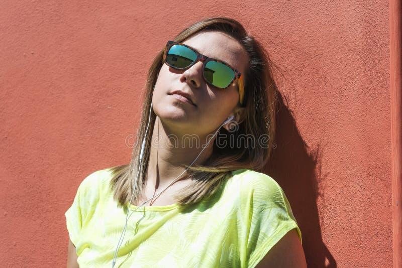 Νέα βέβαια καυκάσια ευτυχής γυναίκα με τα γυαλιά ηλίου και τα ακουστικά πέρα από έναν κοκκινωπό τοίχο στοκ φωτογραφίες