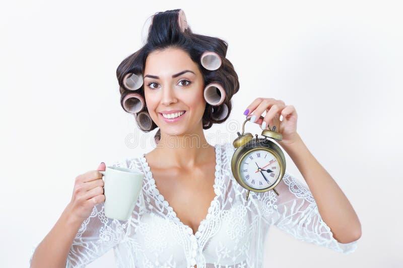 Νέα βιασύνη πρωινού γυναικών με τα ρόλερ καφέ, ρολογιών και τρίχας στοκ εικόνες