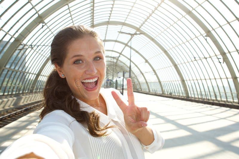 Νέα γελώντας γυναίκα που παίρνει selfie με το σημάδι ειρήνης στοκ φωτογραφία