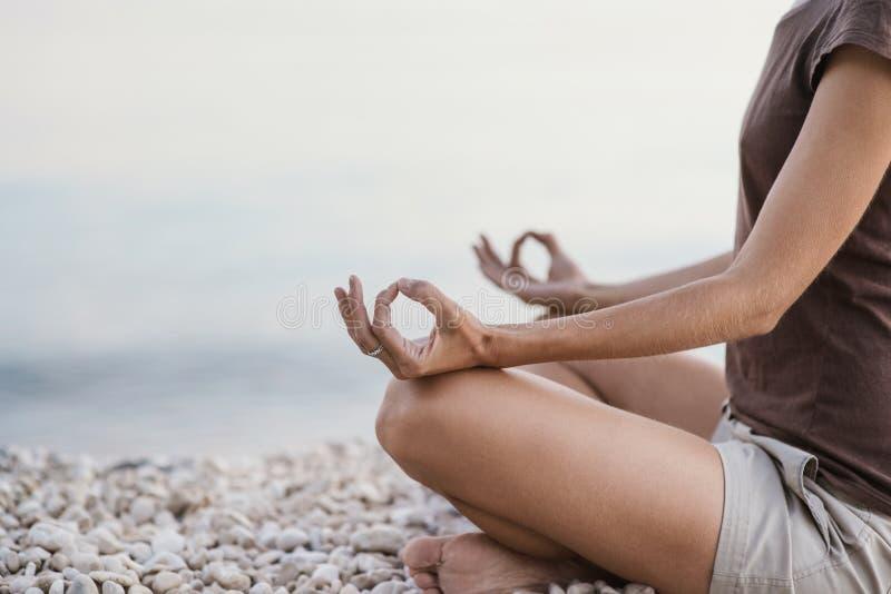 Νέα γιόγκα άσκησης γυναικών κοντά στη θάλασσα Έννοια αρμονίας, περισυλλογής και ταξιδιού Υγιής τρόπος ζωής στοκ φωτογραφία με δικαίωμα ελεύθερης χρήσης