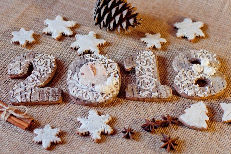 Νέα γλυκά έτους Μπισκότα μελιού, τυποποιημένα ως ξύλινους αριθμούς 2, 0, 1, 8 και άσπρα αστέρια που βάζουν κοντά στις διαφορετικέ στοκ εικόνα