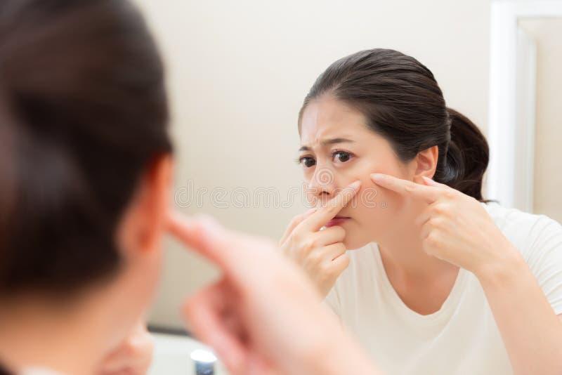Νέα γλυκιά γυναίκα που εξετάζει τον καθρέφτη λουτρών στοκ φωτογραφία με δικαίωμα ελεύθερης χρήσης