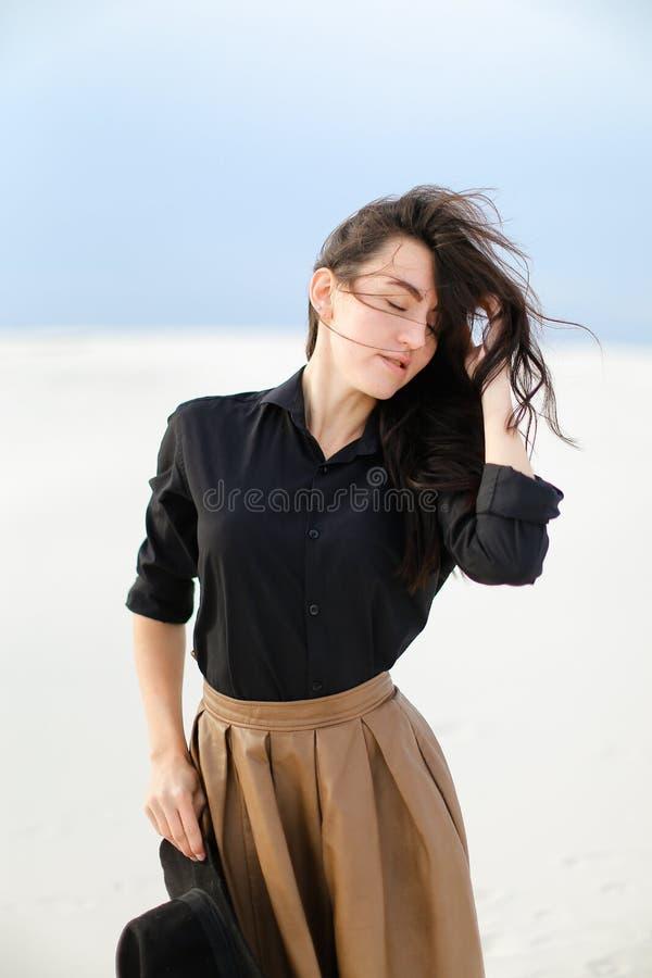 Νέα γοητευτική γυναίκα που φορά τη μαύρη μπλούζα και την καφετιά φούστα που στέκονται στο άσπρο υπόβαθρο και που κρατούν το καπέλ στοκ εικόνες