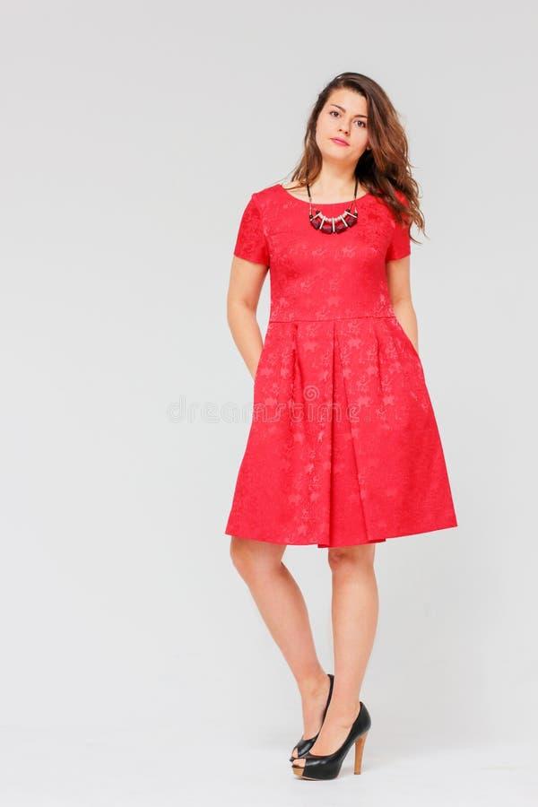 Νέα γοητευτική γυναίκα brunette με τη σγουρή τρίχα στο κομψό κόκκινο φόρεμα στοκ εικόνες με δικαίωμα ελεύθερης χρήσης