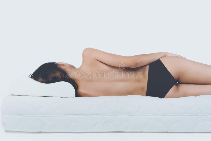 Νέα γυμνή γυναίκα που βρίσκεται στο ορθοπεδικό στρώμα στοκ εικόνες