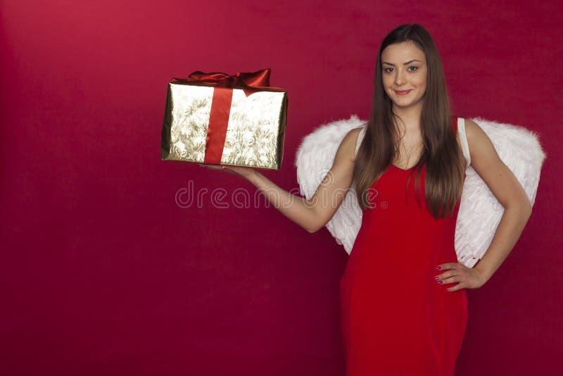 Νέα γυναίκα αγγέλου, όμορφα άσπρα φτερά και ένα θαυμάσιο δώρο στοκ φωτογραφία με δικαίωμα ελεύθερης χρήσης