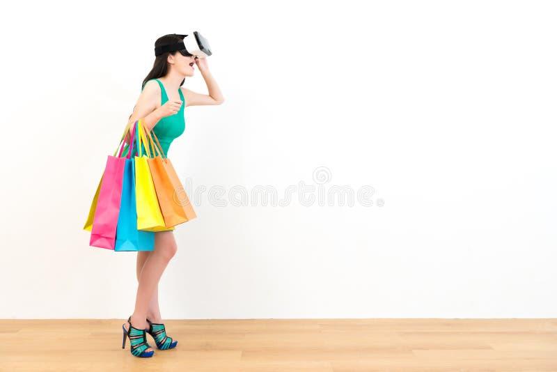 Νέα γυναίκα αγοραστών που φορά τη συσκευή εικονικής πραγματικότητας στοκ εικόνα