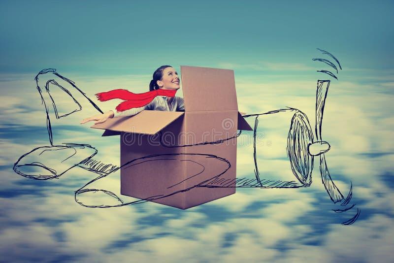 Νέα γυναίκα αεροπόρων με το μαντίλι που πετά το σχεδιασμένο αεροπλάνο στο μεγάλο υψόμετρο στοκ εικόνες