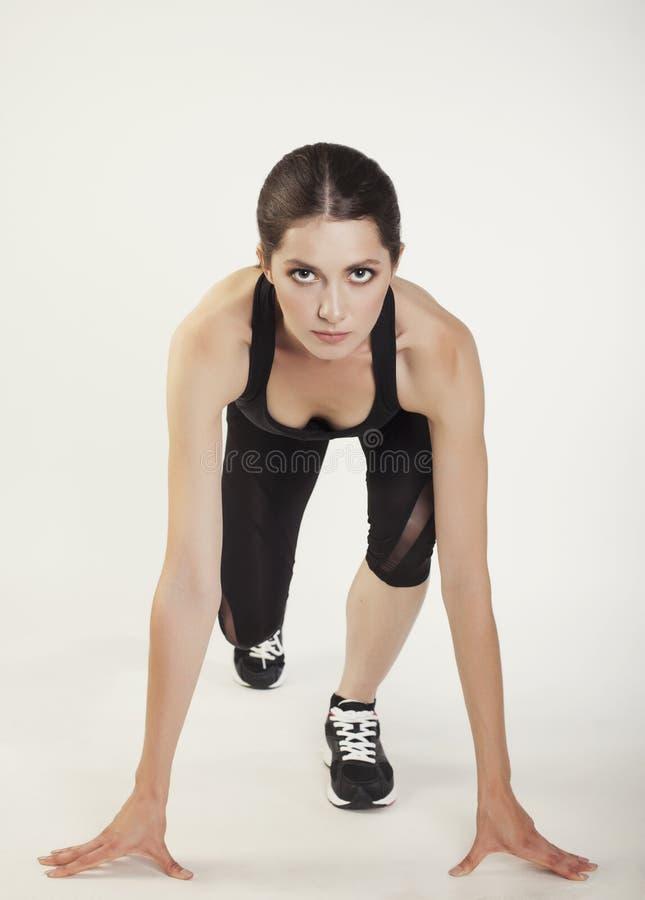 Νέα γυναίκα αθλητικής ομορφιάς στη θέση έναρξης στοκ φωτογραφία με δικαίωμα ελεύθερης χρήσης
