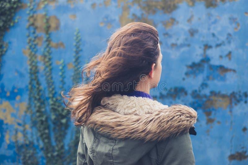Νέα γυναίκα από τον μπλε τοίχο τη θυελλώδη ημέρα στοκ φωτογραφίες